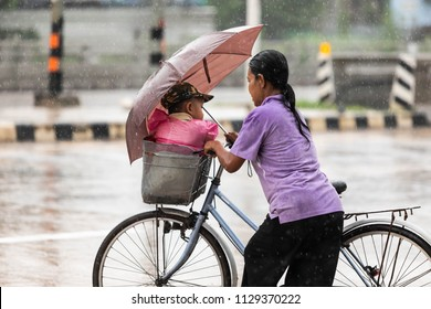 Mae Sot, Tak, Thailand - July 08, 2018 : Unidentified Myanmar woman with a baby in bicycle basket is riding through the rain at Mae Sot, Tak, Thailand.