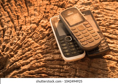 MAE SOT, TAK, THAILAND - MARCH 05, 2018 : Keypad cell-phone brand Nokia placed on the old wooden timber at Mae Sot, Tak, Thailand. The keypad Nokia cell-phone was a very popular in Thailand.