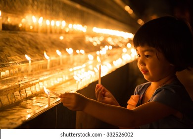 MAE SOT, TAK, THAILAND - OCTOBER28, 2015 : Unidentified Myanmar girl lighting candles to worship the Buddha on the end of Buddhist Lent festival at Wat Thai Watthanaram, Mae Sot, Tak, Thailand