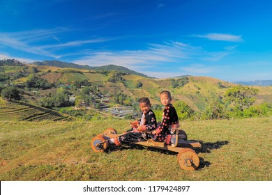 Mae Tho Hill Tribes Village, Chiang Mai -THAILAND, Jan. 10, 2016 : Traditional game in Hmong' s new year, view of Hmong children with traditional dresses playing wooden go cart.