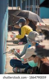 Maehongson School - 15 November 2020 : Volunteers painting artwork on the wall of school building.
