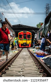 MAEKLONG, THAILAND - JUNE 23, 2018: Famous Thai train market in Maeklong district with train going through railroad in a busy marketplace during a sunny bright day with many tourists around