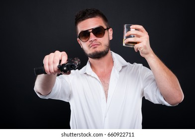 Mafia boss aiming gun or pistol at you while drinking whiskey on dark background