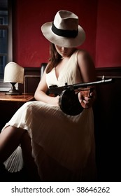 Mafia bride with hat holding a machine-gun