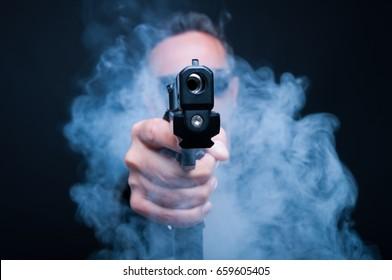 Mafia gunman being ready to shoot somebody thru the smoke on black background