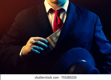 Mafia man in black suit, red tie putting money in pocket on black background.