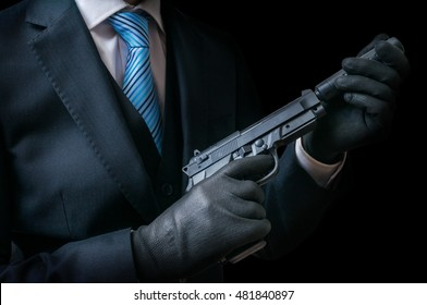 Mafia man or racketeer holds pistol with silincer in hands. Low key photo.