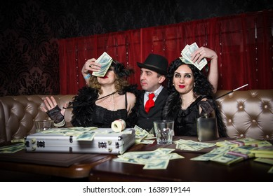 Mafia party in restaurant 1920 style. Elegant girl and man on gangster party. Mafia party in restaurant. Gangsters sitting at the table, party mafia. man and woman share the money won.