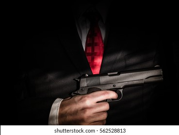 Mafioso holds pulled out gun, isolated on dark background