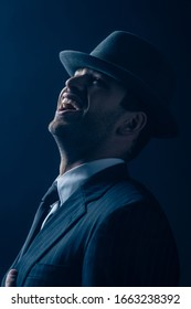 Mafioso in suit and felt hat laughing on dark blue background