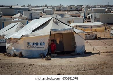 Mafraq, Jordan - June 2, 2014 : Syrian child standing outside her tent at the Zaatari Refugee camp in Mafraq, jordan.