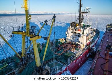 Magadan, Russia - December 29-th, 2015:: Port Magadan, fishing vessel UZON, fishermen work with nets on the deck.