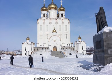 MAGADAN, RUSSIA - MARCH 19, 2018: passersby on the forecourt of the Holy Trinity cathedral, Magadan, Russia.