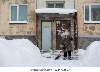 Magadan, Russia - November 23, 2018. A woman with a snow shovel clears a path between the snowdrifts. Hard female work. Janitor cleans the yard near the door to the old panel house.