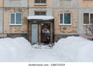 Magadan, Russia - November 23, 2018. Janitor cleans the yard near the door to the old panel house. Hard female labor. A woman with a snow shovel clears the porch.