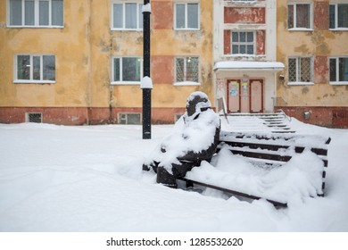 Magadan, Russia - November 23, 2018. Monument to the singer and composer Vadim Kozin. Sculpture of a man sitting on a bench. After the snowfall there is a lot of snow and big snowdrifts in the yard.