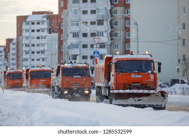 Magadan, Russia - November 24, 2018. Snowplows on the streets of the city. Four orange trucks drive on the road against the background of panel buildings. Around snow and snowdrifts. Cold weather.
