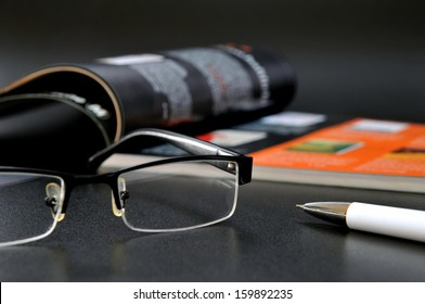 Magazine with glasses and ball pen