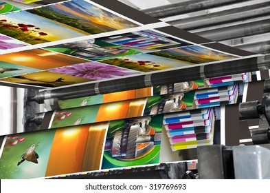 Magazine offset print production line. Large offset printing press running a long roll off paper over its rollers at high speed.