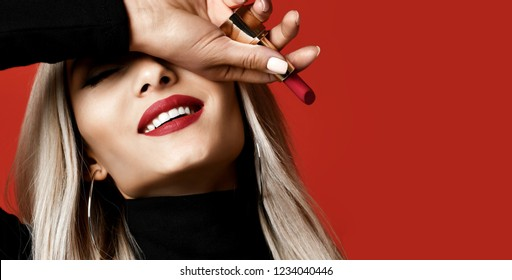 Magazine style composition woman makeup artist hold red lipstick rouge on red background