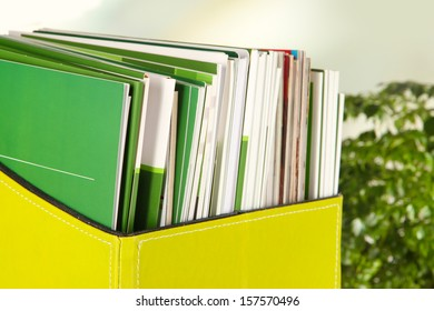Magazines and folders in green box,on office interior background