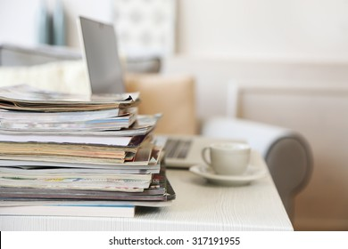 Magazines and laptop on table in living room, close up