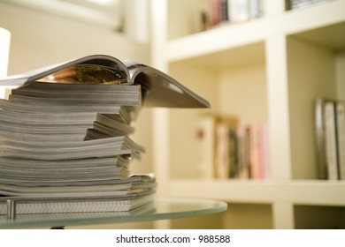 magazines on a crystal table with out of focus interior background