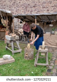 Magdeburg, Germany - 29.08.2014: Kaiser-Otto-Fest. Reconstruction of historical events of the city Magdeburg. Young man chops wood. An impressive holiday for the whole family
