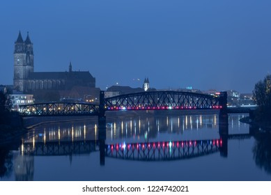 Magdeburg, Germany - 4 November 2018: Nocturnal view of the city of Magdeburg with the cathedral and an old railway bridge, called Hubbrücke, Germany.