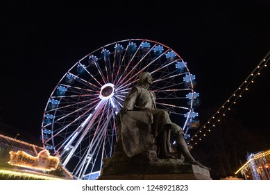 Magdeburg, Germany - December 1, 2018: View of the Otto von Guericke Monument in Magdeburg with a Ferris wheel in the background. The physicist  Guericke became world-famous with his vacuum experiment
