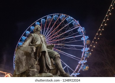 Magdeburg, Germany - December 1, 2018: View of the Otto von Guericke Monument in Magdeburg with a Ferris wheel in the background. The physicist Guericke became world-famous with his vacuum experiments