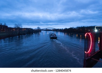 Magdeburg, Germany - January 13, 2019: View of an inland vessel sailing along the Elbe river in Magdeburg at dawn. Nowadays, inland waterway vessels rarely sail on this river.
