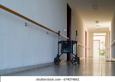 MAGDEBURG, GERMANY – JUNE 12, 2017: long dark hallway and rollator in a dreary nursing home for old people in Magdeburg.