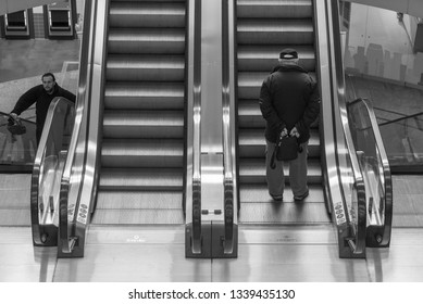 Magdeburg, Germany - March 12, 2019: Two men are driving up an escalator in a shopping center in Magdeburg, Germany.