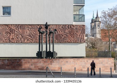 Magdeburg, Germany - March 12, 2019: A man walks along a house opposite the Art Museum of the city of Magdeburg. In the background you can see the Johannis Church.