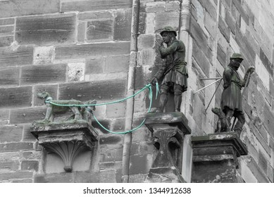 Magdeburg, Germany - March 18, 2019: The shepherd Koppehele with his leashed dogs. Legend says that the shepherd  found a treasure of gold and donated it to build the cathedral of Magdeburg.