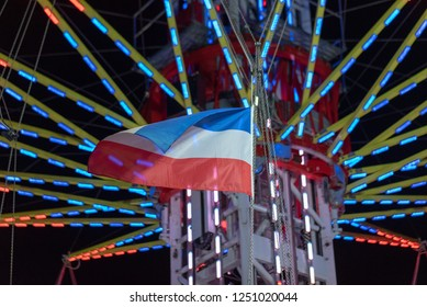 Magdeburg, Germany - November 1, 2018: View of a chain carousel with a blue and white red flag at the Christmas market in Magdeburg, Germany.