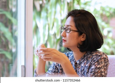 mage of 40s Asian Japanese housewife drinking tea.Beautiful woman wearing eye glasses,lonely with cold cup.She looking outside or flew away.She may be thinking or in trouble.Sad Japanese women concept
