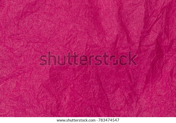 Magenta crumpled paper background. Wrinkled texture of Raspberry wrapping paper