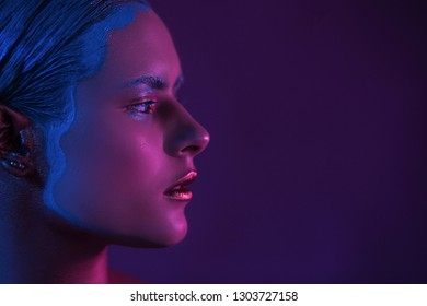 Magenta Half Face of Beautiful Young Girl High Fashion Model in Neon Light on Purple Background. Creative Make Up.