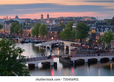 The Magere Brug (also known as Skinny Bridge) is a bridge over the river Amstel in the city centre of Amsterdam, Netherlands. Rooftop view at sunset.