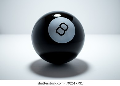 Magic 8 ball from game of billiards or pool dramatically lit from above and isolated from white background.