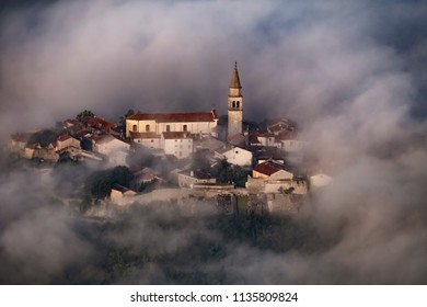 Magic ancient town with walls and bell tower in the clouds. Photo from above. Buzet, Croatia
