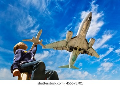 Magic of aviation! Young boy dreaming of becoming a pilot. A child with a toy airplane plays outdoors near airport under the flying in the blue sky aircraft.
