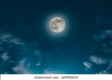 Magic blue night sky landscape with clouds and fullmoon and stars closeup.