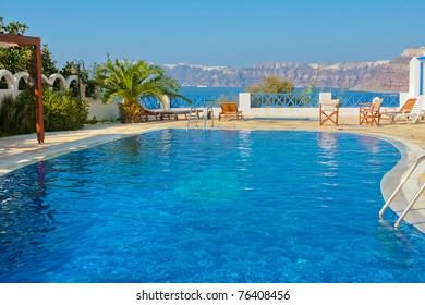 Magic blue swimming pool on island of Santorini, Fira in Greece. Caldera view on a background.