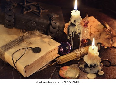 Magic books with wax melted candles, medallions and crystal ball. Halloween still life, fortune telling seance or black magic ritual with mysterious occult and esoteric symbols