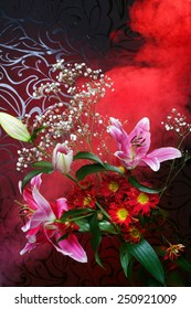 Magic bouquet. Beautiful flowers and color smoke on dark background.