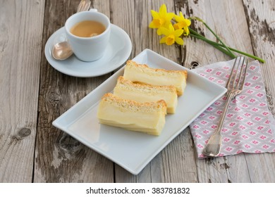 Magic cake - cake made with only one dough - cake with three layers - cheesecake, custard and sponge. With espresso and flowers. Natural light. Selective focus. On wooden table.