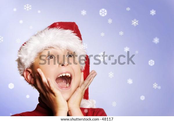 Magic of Christmas.  Boy amongst the snowflakes.